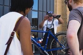Un homme répare un vélo, deux personnes regarde (photo Sven Becker)