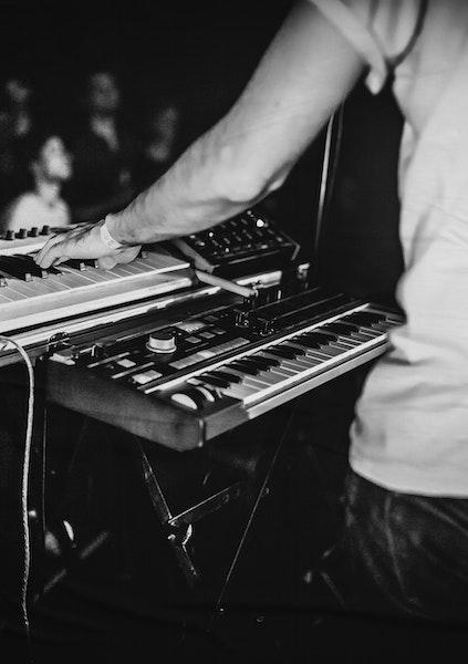 Homme de dos jouant du clavier