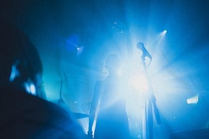 Femme sur scène à contre-jour, lumière bleue, micro à l'avant-plan