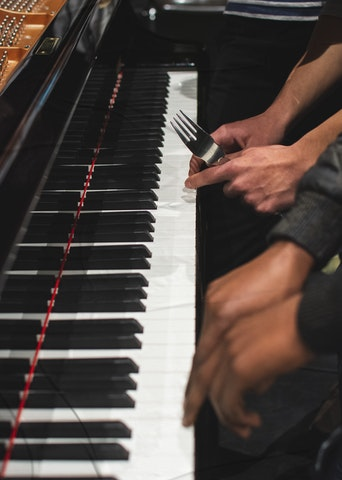 Clavier de piano, quatre mains dont une tient une fourchette