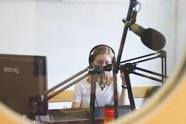 A travers une porte vitrée, une femme dans un studio radio, parle dans le micro avec un casque sur les oreilles