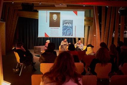 Depuis l'arrière de la salle: le public, trois intervenants assis dont un homme qui parle au micro, projection au mur