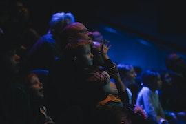 Un homme adulte avec un garçon sur ses genoux au milieu du public dans une salle sombre
