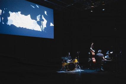 Salle sombre, film d'animation, batterie, contrebasse, piano