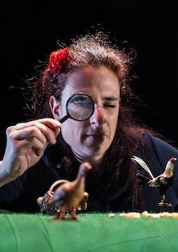 Luisa Bevilacqua tient une loupe. Animaux de basse-cour miniatures à l'avant-plan.