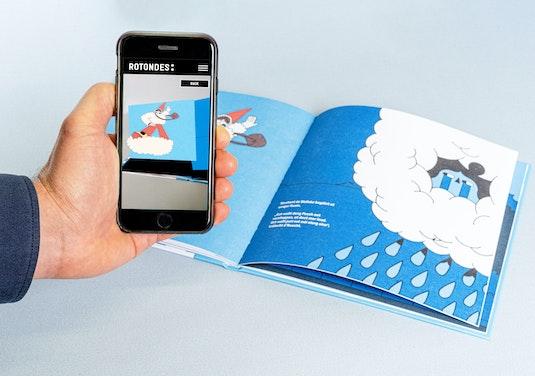 Une main tient un téléphone au-dessus du livre ouvert